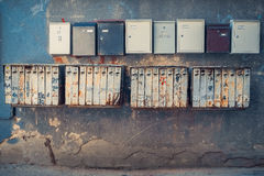 Rows of retro rusty and modern mailboxes on wall. Stock Photo