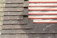 Rows of roof tiles being fitted to wooden battens Royalty Free Stock Photos
