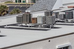 Rows of Rooftop Air Conditioning Units. Rows of many commercial air conditioning and heat pump units on top of a large hotel in Florida to handle the hot and royalty free stock images