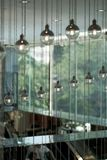 Rows of round decorative lights suspended from the ceiling. In a public building stock photos