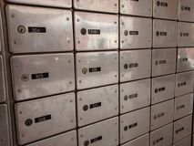 Rows of shiny silver post office boxes, with black number tags. This is a whole wall with mailboxes. They are in shiny silver, with black tags for the numbers Royalty Free Stock Photo