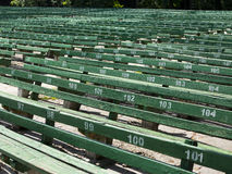 Rows of simple green seats near empty outdoors scene Royalty Free Stock Image