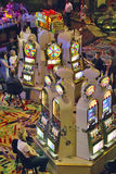 Rows of slot machines and gamblers at Rio Casino in Las Vegas, NV Stock Photos