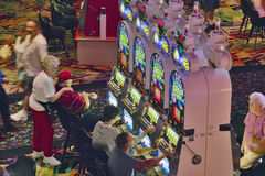 Rows of slot machines and gamblers at Rio Casino in Las Vegas, NV Royalty Free Stock Images