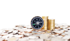 Rows of stack coins and compass. Compass on many money background Stock Photo