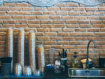 Rows of stacks of upside down transparent plastic coffee cup near stainless steel kitchen sink on brick wall background in cafe. With copy space stock photos