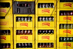 Rows and stacks of yellow Postobon crates and bottles stock photos