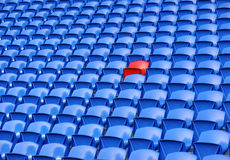 Rows of stadium seating. Single red seat in rows of blue football or soccer stadium seating Stock Photo