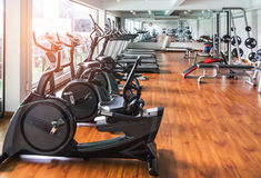 Rows of stationary bikes and health exercise equipment in modern fitness center room Royalty Free Stock Photo