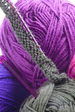 Rows of stitches on a knitting needle. Rows of grey pearl stitches cast on a plastic knitting needle amongst balls of colorful purple, and grey wool showing the Royalty Free Stock Images
