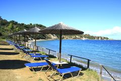 Rows of straw umbrellas and loungeron sandy beach. Greece royalty free stock images