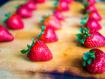 Rows of strawberries on a wooden board. Arranged rows of strawberries on a wooden board Stock Image