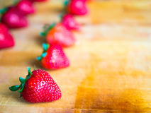 Rows of strawberries on a wooden board with empty space. Arranged rows of strawberries on a wooden board with empty space Stock Photo