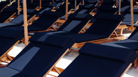 Rows of sunbeds under beach umbrellas at tropical resort Royalty Free Stock Photos