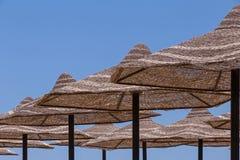 Rows of sunshade straw beach umbrellas Stock Photo