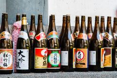Rows of Sake Bottles. Rows of tall, empty, brown sake bottles lined up outside a shrine in Japan Royalty Free Stock Photo