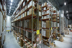 Rows of tall shelves in warehouse. Wide angle shot of large distribution warehouse with tall shelves and racks with packed goods royalty free stock photos