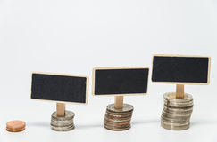 Rows of Thai baht coins and small black board for finance and banking concept with white background and selective focus Royalty Free Stock Photos