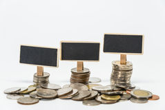 Rows of Thai baht coins and small black board for finance and banking concept with white background and selective focus Stock Photos