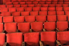 Rows of theater seats with wooden arm rests royalty free stock photos