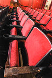 Rows of theater seats with wooden arm rests Stock Photos