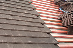 Rows of tiles fixed to wooden battens on roof Stock Images