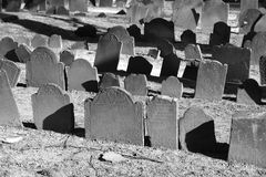 Rows of tombstones bathed in sunlight, old graves in bright sunlight. Ancient grave stones in black and white in bright sun light on a beautiful winter's day Royalty Free Stock Photos