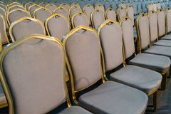 Rows of traditional hard wood chairs with soft cushion and golden edging for formal meetings, conference, lectures, graduation ce. Remonies stock photo