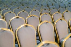 Rows of traditional hard wood chairs with soft cushion and golden edging for formal meetings, conference, lectures, graduation ce. Remonies royalty free stock image