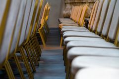 Rows of traditional hard wood chairs with soft cushion and golden edging for formal meetings, conference, lectures, graduation ce. Remonies stock photography