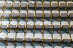 Rows of traditional hard wood chairs with soft cushion and golden edging for formal meetings, conference, lectures, graduation ce. Remonies royalty free stock photos