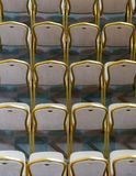 Rows of traditional hard wood chairs with soft cushion and golden edging for formal meetings, conference, lectures, graduation ce. Remonies stock image