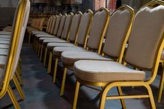 Rows of traditional hard wood chairs with soft cushion and golden edging for formal meetings, conference, lectures, graduation ce. Remonies royalty free stock photo