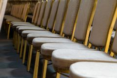 Rows of traditional hard wood chairs with soft cushion and golden edging for formal meetings, conference, lectures, graduation ce. Remonies royalty free stock photography