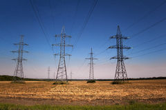 Rows of transmission towers and power lines in the field. In the countryside Royalty Free Stock Images