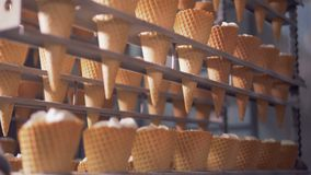 Rows of waffle cones are getting lifted and lowered by a factory mechanism. 4K stock video