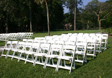 Rows of white chairs. For wedding guests in country setting stock photography