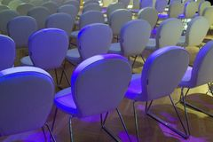 Rows of white chairs for audience stock photography