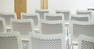 Rows of white chairs in empty convention hall. Rows of white chairs in modern empty convention hall stock footage