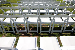 Rows of white chairs outdoors for ceremony Stock Image