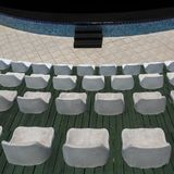 Rows of white chairs and a stage in an outdoor auditorium or hall for carrying out presentations Stock Photo