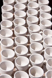 Rows of white cups from clay Stock Photos