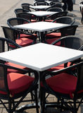 Rows of white empty tables and black wicker chairs in an open air cafeteria. Stock Photos