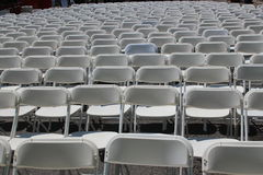 Rows of white folding chairs at a concert, wedding, festival or gathering Royalty Free Stock Photography