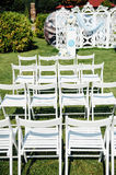 Rows of white folding chairs on lawn Stock Photo