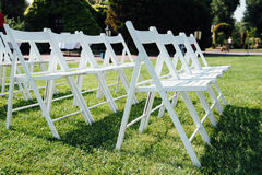 Rows of white folding chairs on lawn Royalty Free Stock Image