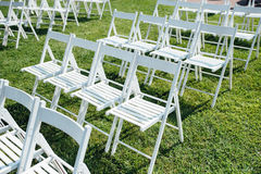 Rows of white folding chairs on lawn Stock Images