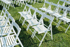 Rows of white folding chairs on lawn Stock Photos