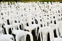 Rows of White Plastic Outdoor Chairs. Many white plastic outdoor furniture chars in rows after an outdoor concert or performance, some with post concert litter royalty free stock photos