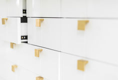 White sleek drawers with golden handles. Stock Photo